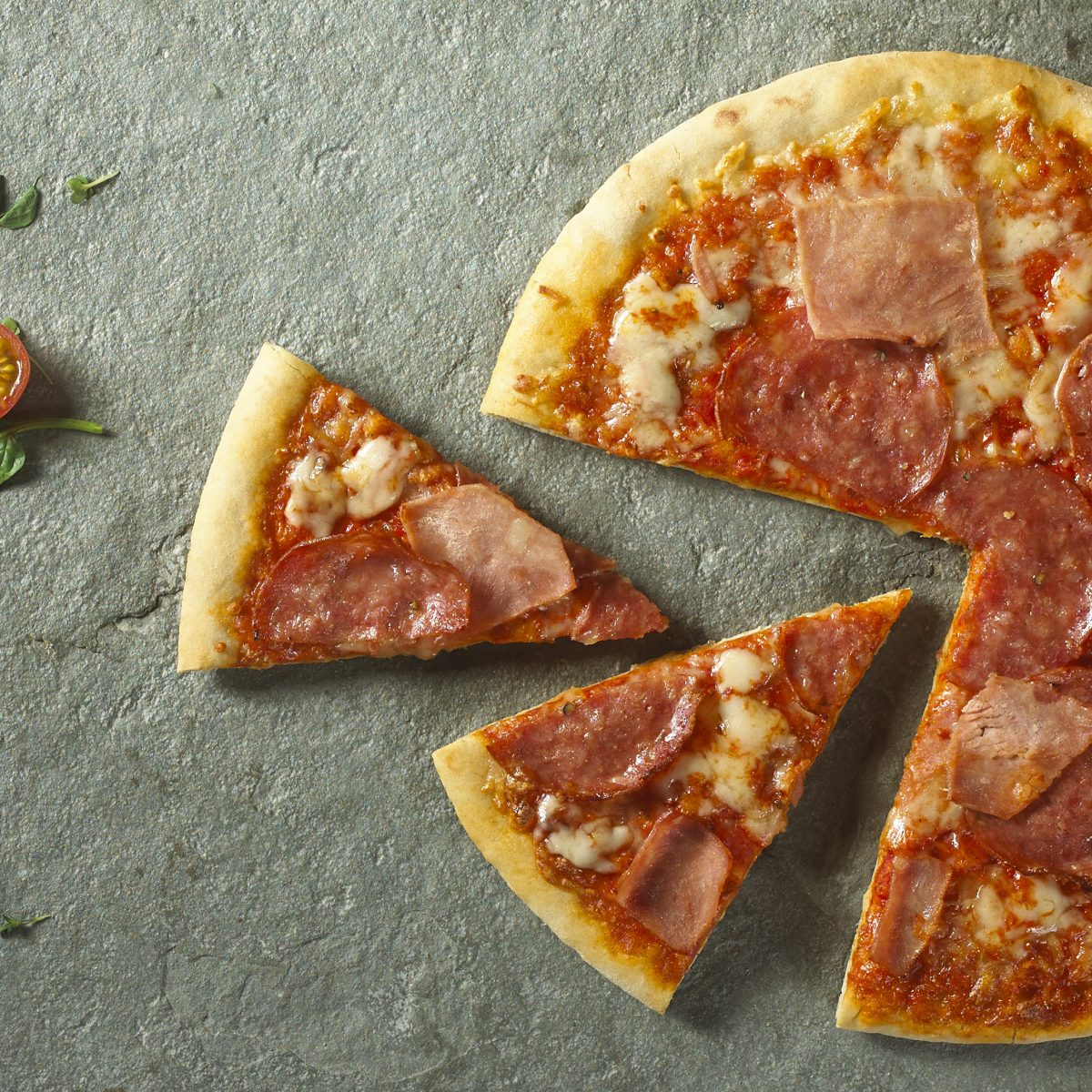 Hand stretched Italian stonebaked pizza with mozzarella, tomatoes, ham and salami